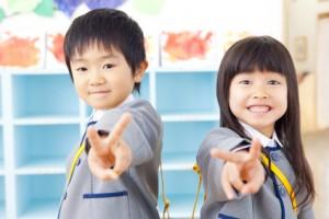 ピースサインをする幼稚園児男女